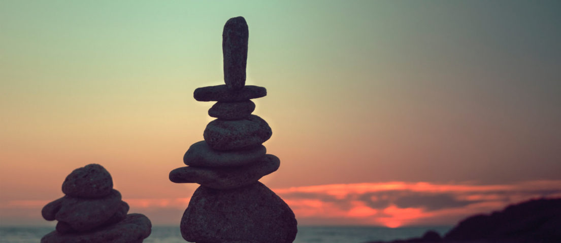 stones stacked and balancing in front of sunset